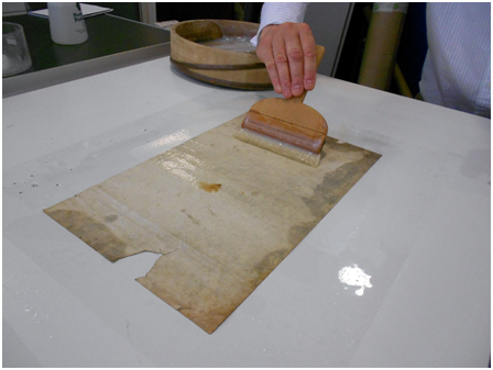 Lining a print. After the object was humidified, it was placed on a sheet of Melinex. The verso of the object was pasted with wheat starch paste using a Japanese brush.